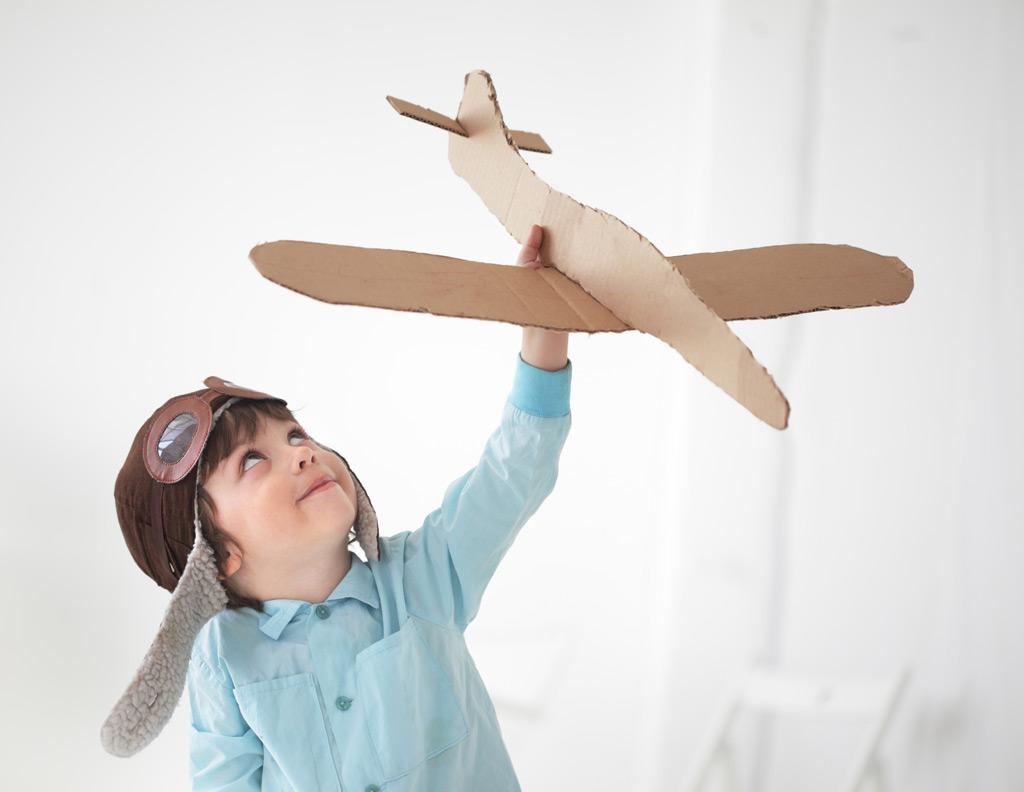 Фото: Счастливый мальчик играет с самолетом